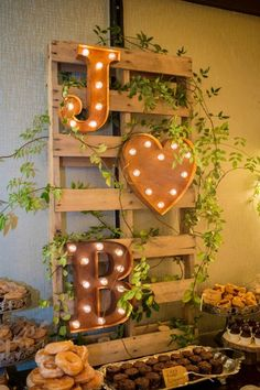 Marquee light monogram mounted on wooden pallet to create dessert bar sign