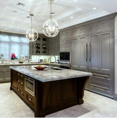 Kitchen - cabinets painted BM Timber Wolf with glass knobs - large island with super white quartz couter top - beautiful pendants - impressive room | Signature Interior Design
