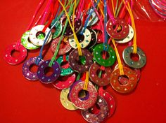 Paint washers with layers of nail varnish and decorate with glitter. Seal with clear nail varnish and string on nylon craft strings.
