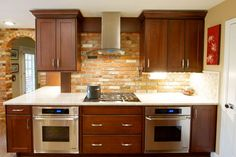 Existing brick wall used as feature  for new cooking zone with under counter ovens, gas cooktop & hood.  Cherry cabinets with black glaze, granite, brushed nickel hardware. Audrey Michel Photography.