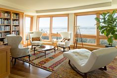Crazy about this ocean front family room:  love the three matching wing back chairs  in linen and cowhide + elegant lounge chair w/sheepskin throw (all in white); layered rugs; built-in book case; bare windows