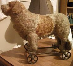 VINTAGE ANTIQUE DOG ON WHEELS STRAW AND MOHAIR.  Looks like a Newfie or maybe a Saint Bernard.