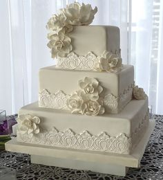 Three tree square wedding cake with sugar paste Gardenia flowers wrapped in lace fondant banding