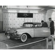 Side view of salesman showing car to customer in showroom Canvas Art - (24 x 36)