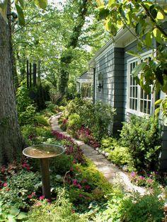 Un piccolo sentiero sinuoso e sereno in pietra definito da una combinazione di fiori e piante caratterizzate da fogliame dorato, fioriture viola e spruzzi di magenta, che contrastano con le pareti di questo cottage