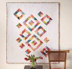 This quilt was inspired by a rainbow of bright Kaffe Fassett fabric scraps. The white Kona Cotton to gives the quilt a crisp, clean look. The half-square triangle units create what appeared to be floating squares.