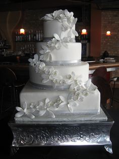 White Wedding Cake with rhinestones and orchids...possibly with plum colored ribbon instead of the silver