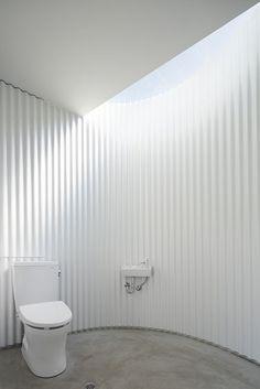 清潔感をつくる曲面の壁 群馬県中之条町の中心市街地の公衆トイレを建て替えるプロジェクト。敷地は林昌寺という中之条に古くからあるお寺の駐車場の一角である。アートの町に相応しい町のシンボルになるようなものであると同時に、公衆トイレの陰気な雰囲気をなくし明るく快適なトイレとすることが望まれていた。公衆トイレという性格上メンテナンスの問題から木材を多用するといった方法ではうまくいかない。そこで、空間の陰影をデザインすることで陰気さを取り払うことを考えた。通常の矩形のトイレでは、空間の角に影ができそこに水や汚れ、時には蜘蛛の巣がはって陰気な雰囲気をつくりだす。この角をなくし、トップライトからの自然光が室内の壁をやわらかく照らすことで、明るく快適な空間が公衆トイレでも実現できると考えた。 人の流れと距離感を作るかたち…