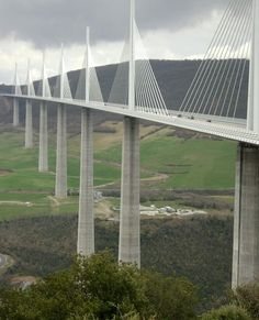 The tallest bridge in the world, the Millau Bridge, spans the valley of the river Tarn near Millau in southern France;  one mast's summit is 1,125 feet above the base of the structure;  it has the 12th highest bridge deck in the world at 890 feet above the ground;  photo by Roland Nizet