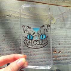 """Cheshire Cat Alice in Wonderland iPhone 5S/5G Case Clear, thin, flexible iPhone 5S/5G case.  Reads, """"We're All Mad Here.  Still in original packaging.  Cheshire Cat from Alice in Wonderland.  Turquoise and black lettering.  The clear case is indeed clear but has a screen texture, hard to describe but visible in the up close photos of the bottom and side. Accessories Phone Cases"""