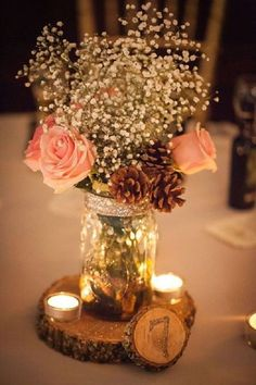 Here is cute Mason jar and tea light holder can place on round rustic wooden pallet. This Mason jar is filled with rose baby breath flowers and pine cone.