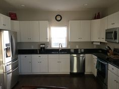 I LOVE my new kitchen! Mannington Hickory plank in Cocoa laminate floor White shaker cabinets. Black pearl granite. Samsung stainless appliances. Sherwin Williams Worldly Gray wall paint.