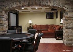 This man cave not only has a poker table, but a large sitting area to watch TV. The arched stone wall is a pretty nice touch too. Click to see how much it costs to build an addition to your home.