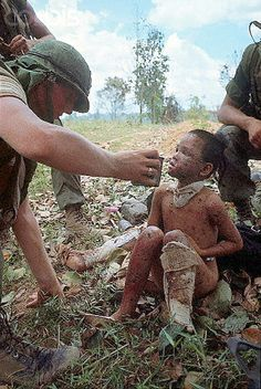 19 May 1967, Con Thien. 19 May 1967, Con Thien, South Vietnam --- Picture shows a US Marine giving a young Vietnamese boy some water and medial attention. He body was burned after the Leathernecks swept through his village.