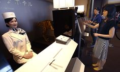 A receptionist robot greets a hotel employee, demonstrating how to check in at the new hotel, aptly called Weird Hotel, in Sasebo, south-western Japan.