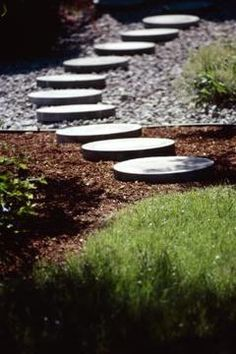 Round paver stones used for a garden walkway create a visually interesting juxtaposition with the straight, square sides of the walkway outline. Many companies that sell concrete mix also sell molds f River Rock Landscaping, Landscaping With Rocks, Backyard Landscaping, Landscaping Ideas, Backyard Ideas, Walkway Ideas, Outdoor Ideas, Walkway Designs, Stone Landscaping
