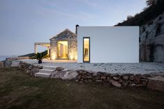 Architects Valia Foufa and Panagiotis Papassotiriou, have designed Villa Melana, a new contemporary country house overlooking the water in Tyros, Greece.