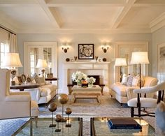 Gorgeous tonal living room by Joseph Kreme in a Hamptons home designed by Shope Reno Wharton. Love the combination of the whisper grey walls, cream mouldings, and cream furniture, combined with pops of metallic from the side and coffee table and the art. A nice symmetry is underscored by the Chesterfield sofas, double sconces over the mantel and french doors to either side of the fireplace. A lovely composition.