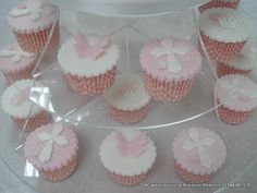 Selection of Baptism cupcakes on a cupcake tower. The cupcakes are iced in either pink or white with a butterfly or cross. Finished with pink gingham cases