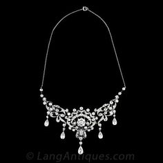 This antique bib style necklace from the 1890's is very early Edwardian. The floral and scroll motifs are fully diamond set with five pear shaped diamond set pendants. As with many pieces made at this time you can also see the influence of the Art Nouveau movement with the use of curvilinear lines. This beautiful necklace set with 4.60 carats of European and Swiss cut diamonds is fitting for a very special occasion.
