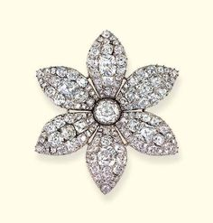 The Queen`s Six Petal Diamond Flower brooch. This brooch is designed as a clematis flower & is composed of six old-cut, pave-set diamond petals. Each petal has a large row of diamonds down the centre. The petals surround a large round single diamond collet, mounted in silver with a closed back setting. The brooch is 6.5cms wide. Princess Elizabeth wore this brooch in her engagement photo.