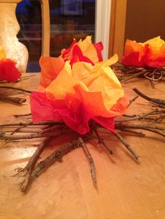 Campfire made of sticks and tissue paper. Super easy. Found all these sticks on a walk with my Cub Scout son. Glue together criss cross in random pattern and insert red, yellow, orange tissue paper squares into center. Glue gun works wonders.