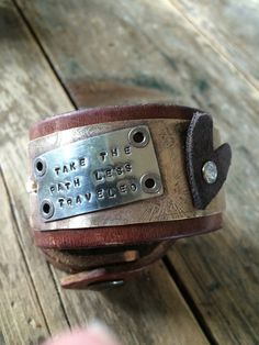 Handcrafted Leather cuff. I have soldered riveted a plate stamped with TAKE THE PATH LESS TRAVELED onto an etched brass plate. I also riveted a soft