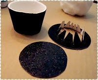 Mini top hat, no fabric, no sew: Use a small Styrofoam coffee cup as base. Remove the bottom of the cup and then cut the height of the cup down. Using the black glitter paper cover the cup, see above, then cut out the rim and top of the hat. Simply assemble this with glue. I found that for this the glue gun did not work well, I would suggest another strong fast drying glue. Once the hat was dry, trim with ribbon, and little holly leaves from felt and red beads for berries and snow glitter.