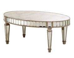 "With mirrored legs and a gemlike border, this 48.5""-wide table sparkles."