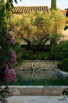 DESIGNER MICHEL SEMINI, PROVENCE, FRANCE. LIMESTONE POOL WITH WATER SPOUT IN THE EVENING