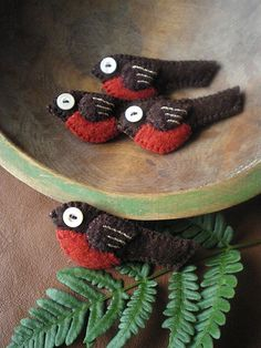 I finished sewing a handful of wee wool robin pins this morning.  They're made of a combo of handmade wool felt and sweater wool.  They have little vintage button eyes.