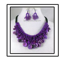 Black strips of fabric is crochet with purple thread and beads to make this necklace and earring jewelry set. The necklace ties in back and adjusts up to 38 inches. The earrings measure about 1 1/2 inches long. Thanks for shopping  A metal jewelry finding can be added to the necklace for an additional fee of $3.00. Send me a conversation for the exact details before finalizing the purchase
