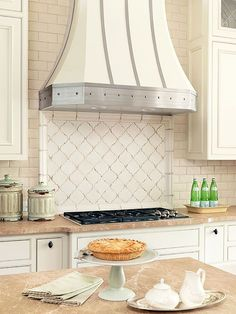 cream tiles behind the range are situated in an arabesque pattern and contrast horizontal subway tiles