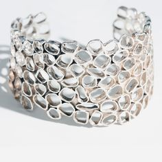 Urban Beehive by Shauna Burke. Sterling silver hand fabricated cuff measures 2 inches at its highest point.