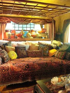 A living area to entertain friends with vibrant pillows in different shapes and sizes, wooden frames on windows and lots of natural light <3