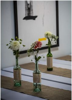 Wine bottle vases. Simple. Classy. Easy. Inexpensive. Plus it has a vintage feel. Wrap with twine to make it perfect.