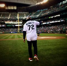 Michael Bennett throwing the first pitch out at Mariners game tonight.beard hat night at the ballpark! Seahawks Team, Seattle Seahawks, Michael Bennett, Beard Hat, 12th Man, Baseball Field, Pitch, Football, Game