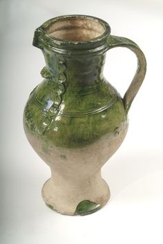 'Tudor Green' ware anthropomorphic baluster jug with green glaze. This is an example of a buffware with thick glassy darkgreen glaze, it has a degenerate mask decoration on the front. This type of jug was produced in Surrey. White-firing, sandy earthenwares were one of the main kinds of pottery used in London and its environs from the middle of the 13th until the 16th century. They were made at a number of sources in Surrey and along the Surrey-Hampshire borders.    Date:  1350 AD - 1500 AD