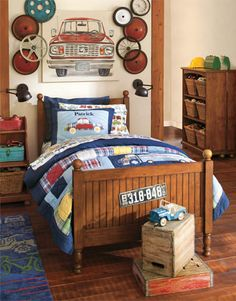 A car theme creates a fun opportunity to mix playful vintage elements in this room. We created a unique wall display with a collection of reclaimed wheels, hung alongside artwork featuring an antique car that looks like it's about to enter the room. Bedding in bright primary colors with a madras accents has a versatile palette that makes it easy to accessorize.