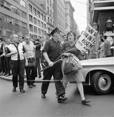 """Woman demonstrator carrying a paper bag and a torn placard is escorted by New York City policeman in the area of Fifth Avenue and 47th street on August 15, 1964. She was one of 250 demonstrators who attempted to hold a rally in Duffy Square to protest U.S. action in Vietnam. They were battled by police and about thirty arrests made when they attempted to walk towards the United Nations headquarters. Rally was called by the """"May 2 Movement"""" and """"Youth against War and Fascism"""" organizations…"""