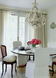 dreamy! Large round mahogany pedestal dining table in front of French door windows; cane back dining chairs along with slipcovered dining chairs; 140411