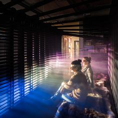 Visitors to an exhibition of work by architects Haptic can take a rest inside a wooden cabin filled with coloured light and smoke