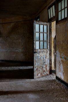Decaying wards at abandoned hospital, open door; Verden Psychiatric Hospital © opacity.us