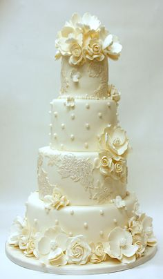 Four-tiered white wedding cake with touches of very light gold. Sugar paste flowers are scattered about and also make a lovely topper.