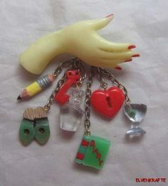 Vintage carved Bakelite hand brooch with seven dangling charms. #vintage #jewelry #brooches