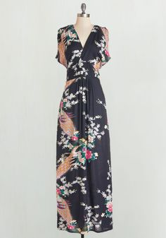 Glide through your day feeling dreamy as can be in this printed maxi dress! An ethereal print of illustrated bouquets and stunning peacocks adorns the soft black silhouette of this V-necked, short-sleeved frock, creating a look that is both vibrant and poised.