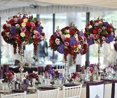 These regal centerpieces are formed with purple hydrangeas, classic roses in red, pink and white tones and bunches of grapes.