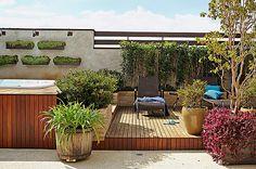 Cobertura | Rente ao muro, jardineira de tijolos aparentes com murtas. Entre os degraus que levam ao spa, gardênias. Em primeiro plano, tina de madeira com agapanto.