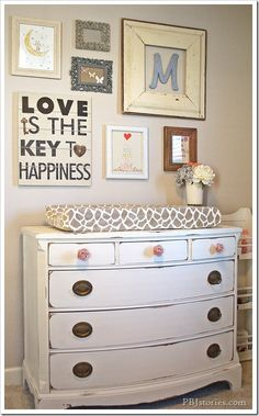 What a great makeover! A covered pad is added to the top of a dresser that has been distressed & the dresser is now used as a baby changing table. I love the drawer hardware! The wall decor is great, as well!