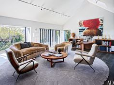 A large artwork by Jack Pierson presides over film and TV producer Brian Grazer's California home office, where a plush sofa and chair and a wood cocktail table—all vintage pieces by Jean Royère—are joined by midcentury armchairs from France (left) and Italy; the rug was custom made by Mansour Modern.